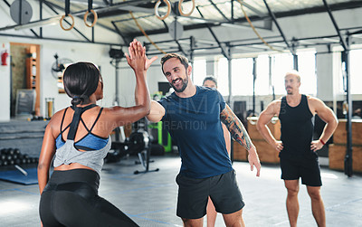 Buy stock photo Cropped shot of two young athletes high-fiving during a workout in the gym