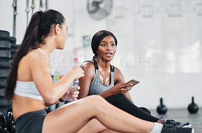 Buy stock photo Shot of two young women talking while sitting together at the gym