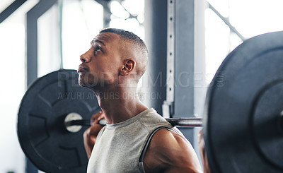 Buy stock photo Cropped shot of a young man working out with a barbell at the gym