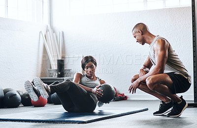 Buy stock photo Shot of a woman working out with the help of her coach at the gym