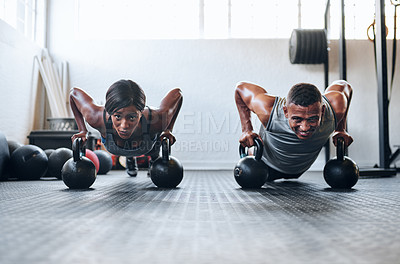 Buy stock photo Shot of two young athletes working out using kettle bells at the gym