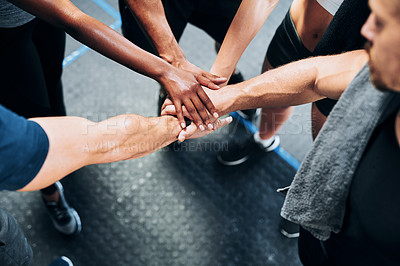 Buy stock photo Shot of a group of people joining their hands together while working out at the gym