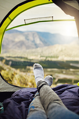 Buy stock photo Shot of an unrecognisable woman relaxing in a tent out in nature