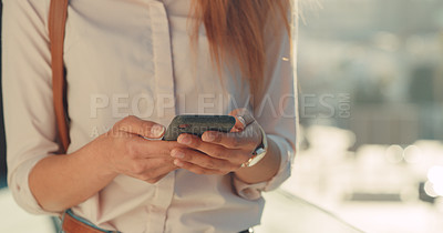 Buy stock photo Cropped shot of an unrecognizable young woman using her cellphone while standing outside in the city