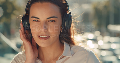Buy stock photo Cropped portrait of a beautiful young woman listening to music while standing outside in the city