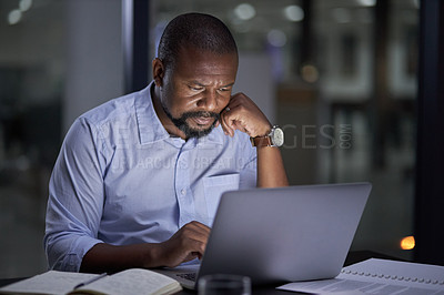 Buy stock photo Shot of a mature businessman working on a laptop in an office at night