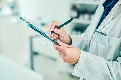 Buy stock photo Shot of a scientist filling out paperwork in a laboratory