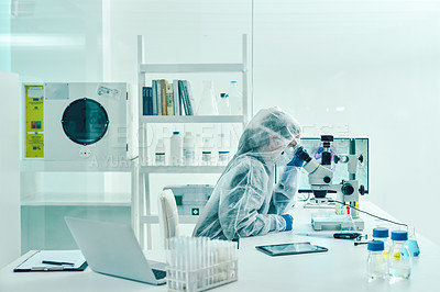 Buy stock photo Shot of a scientist wearing a hazmat suit and using a microscope in a laboratory