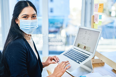 Buy stock photo Portrait of a young businesswoman wearing a face mask while working on a laptop in an office