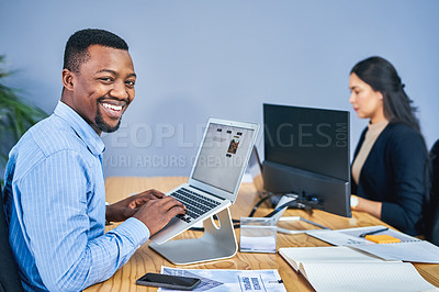 Buy stock photo Portrait of a young businessman working on a laptop in an office with a colleague in the background