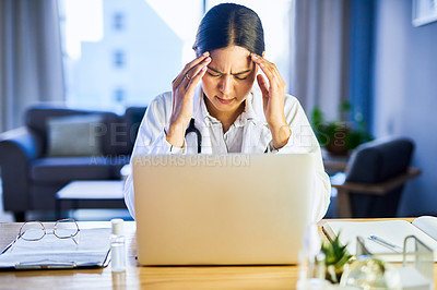 Buy stock photo Shot of a young doctor looking stressed out while using a laptop in a modern hospital