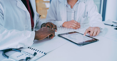 Buy stock photo Shot of two doctors using a digital tablet during a discussion in a clinic