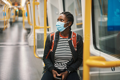 Buy stock photo Shot of a young woman wearing a face mask while traveling on a bus