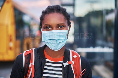 Buy stock photo Shot of a masked young woman walking through the city