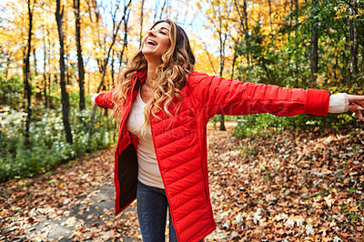 Buy stock photo Cropped shot of an attractive young woman standing with her arms outstretched in the forest during autumn