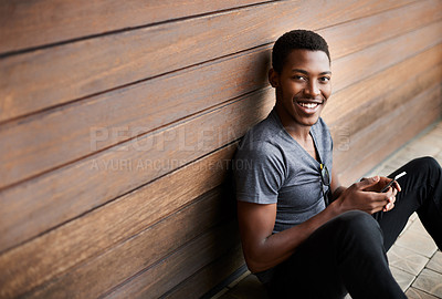 Buy stock photo Portrait of a stylish young man using a cellphone while sitting against a wooden background
