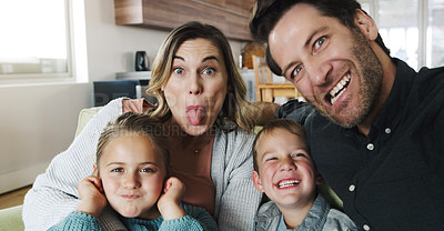 Buy stock photo Shot of a happy young family taking fun selfies on the sofa at home