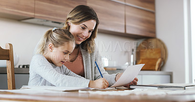 Buy stock photo Shot of a young woman helping her daughter with homework at home