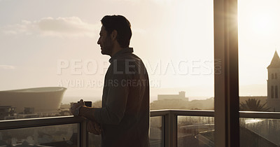 Buy stock photo Shot of a young man having a cup of coffee while standing on the balcony of his apartment