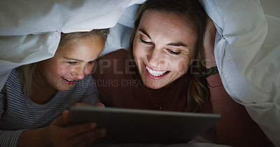 Buy stock photo Shot of an adorable little girl using a digital tablet with her mother at bedtime
