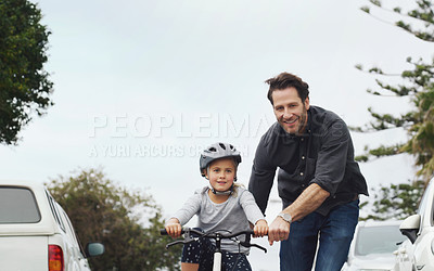 Buy stock photo Shot of an adorable little girl learning how to ride a bicycle with help from her father
