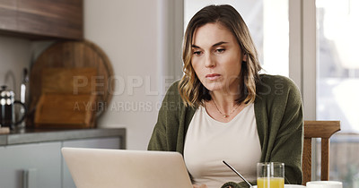 Buy stock photo Shot of a young woman using a smartphone while having breakfast at home