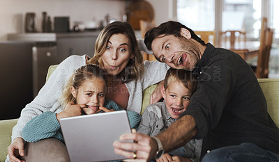 Buy stock photo Shot of a happy young family taking selfies with a digital tablet on the sofa at home