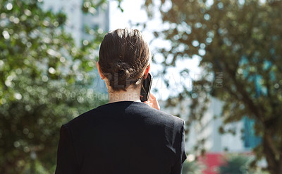 Buy stock photo Shot of a young businesswoman using a smartphone in the city