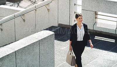 Buy stock photo Shot of a confident young businesswoman walking through the city