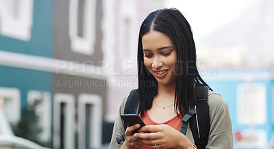 Buy stock photo Shot of a happy young woman using a smartphone while exploring a city