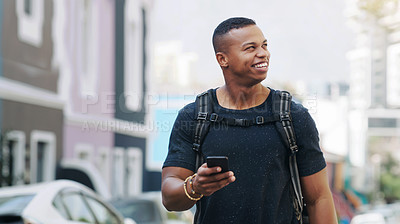 Buy stock photo Shot of a happy young man using a smartphone while exploring a city