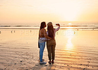 Buy stock photo Shot of a young woman and her mother taking a selfie at the beach