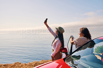 Buy stock photo Shot of a young woman and her mother taking pictures at the beach while out on a road trip