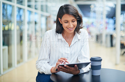 Buy stock photo Shot of a young businesswoman using a digital tablet during a coffee break in a modern office