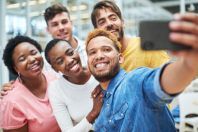 Buy stock photo Shot of a group of young businesspeople taking a selfie together in a modern office