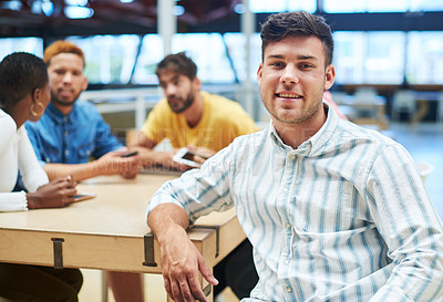 Buy stock photo Shot of a young businessman having a meeting with his team in a modern office