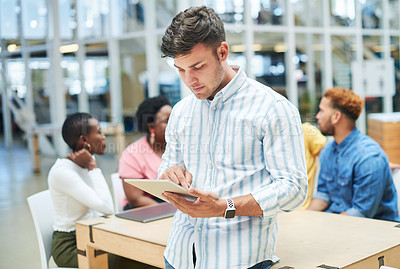 Buy stock photo Shot of a young businessman using a digital tablet during a team meeting in a modern office
