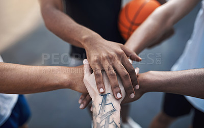 Buy stock photo Closeup shot of a group of sporty young men joining their hands together in a huddle on a sports court