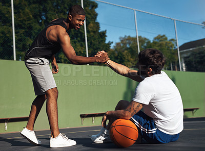 Buy stock photo Shot of two sporty young men shaking hands on a basketball court