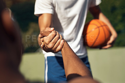 Buy stock photo Closeup shot of two sporty young men shaking hands on a basketball court