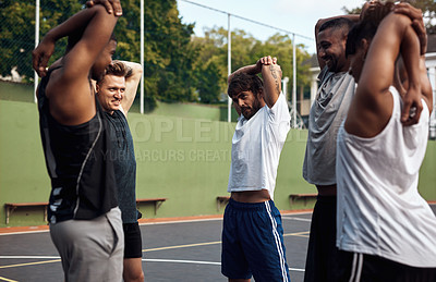 Buy stock photo Shot of a group of sporty young men stretching their arms on a sports court