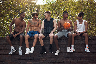 Buy stock photo Shot of a group of sporty young men sitting on a wall after a game of basketball