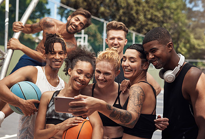 Buy stock photo Shot of a group of sporty young people taking selfies together on a sports court
