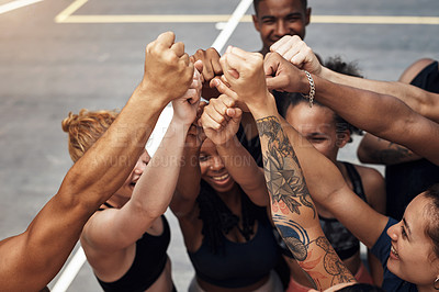 Buy stock photo Shot of a group of sporty young people standing together in a huddle on a basketball court