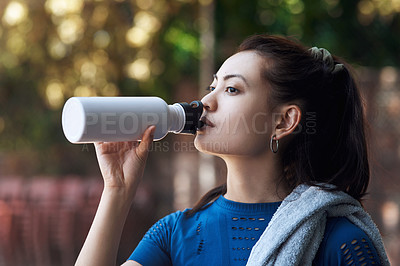 Buy stock photo Cropped shot of an attractive young female athlete drinking water while standing on the basketball court