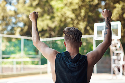Buy stock photo Rearview shot of a sporty young man cheering on a sports court