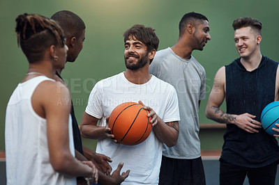 Buy stock photo Shot of a group of sporty young men hanging out on a basketball court