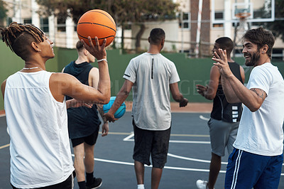 Buy stock photo Rearview shot of a group of sporty young men hanging out on a basketball court