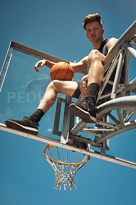 Buy stock photo Portrait of a sporty young man sitting on a basketball hoop on a sports court