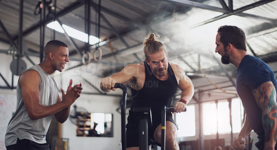 Buy stock photo Shot of a young man working out on an exercise bike while his friends encourage him in a gym